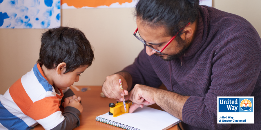 Image of a father showing his son how to trace objects.