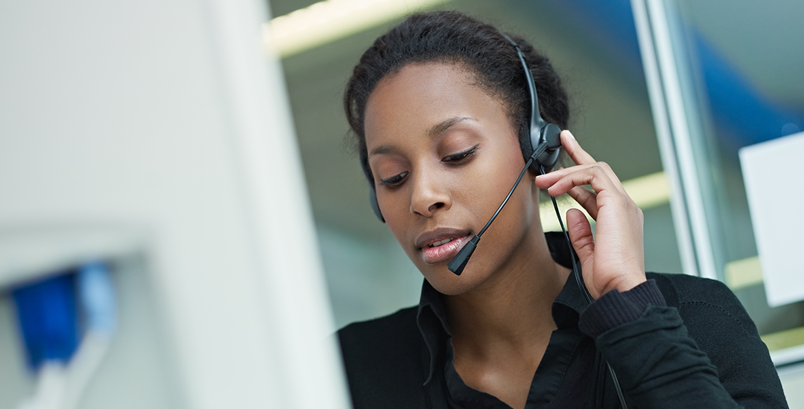A call specialist wearing a headset speaks to someone on the phone