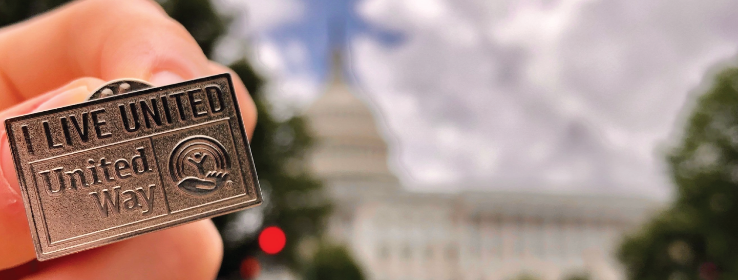Hand holding a UnitedWay gold pin with the white house in the background