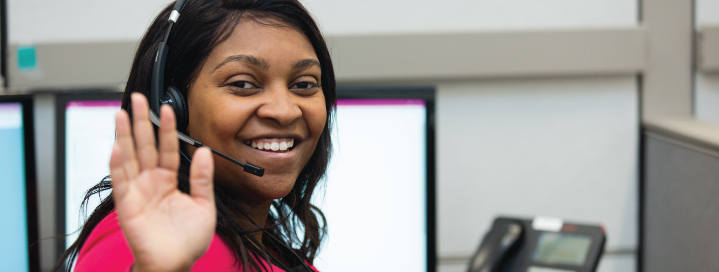Woman from United Way of Greater Cincinnati 211 call center waving and smiling