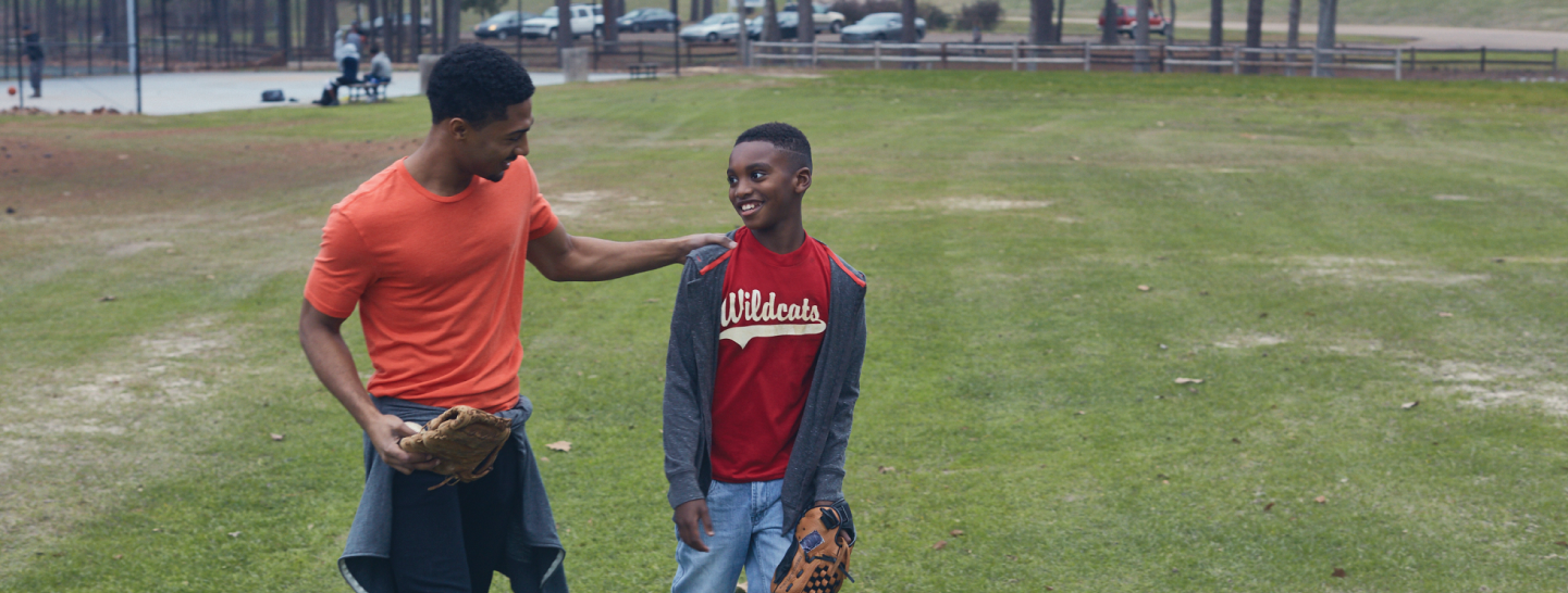 Young man with his hand on a child's shoulder as they walk across baseball field