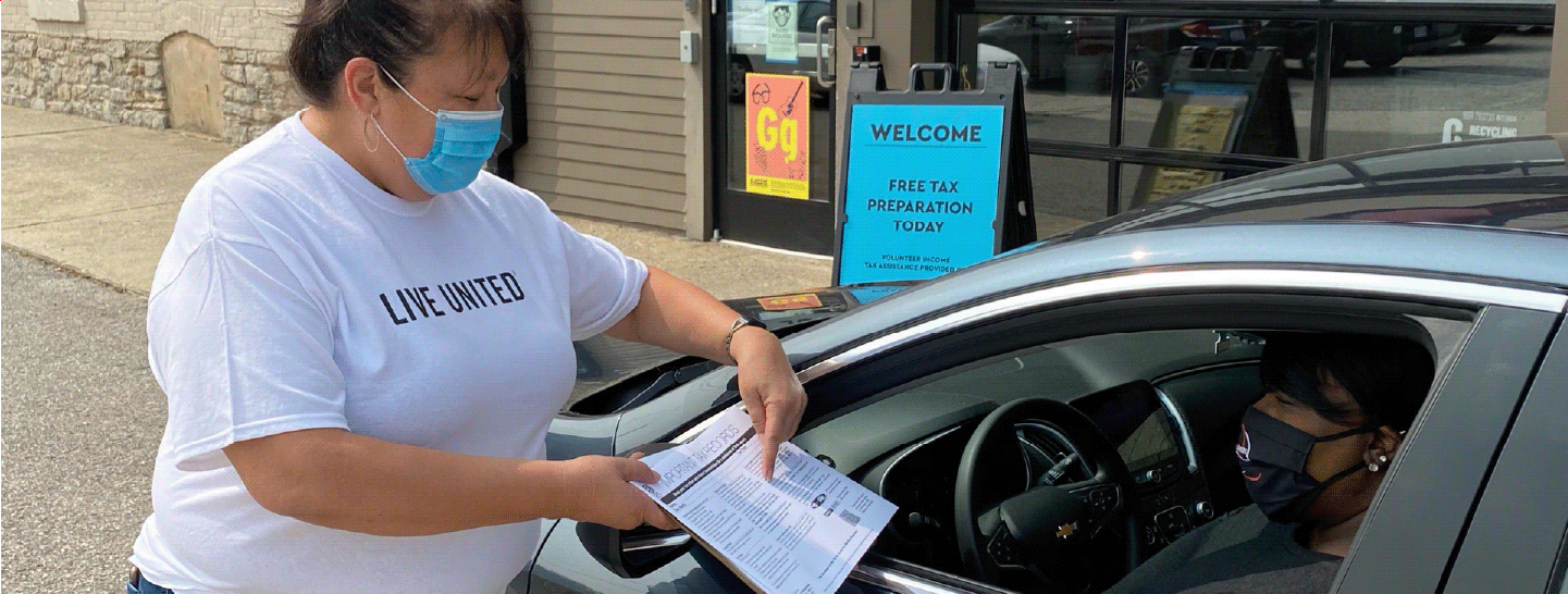A volunteer wearing a mask helps a woman with her taxes while in her car
