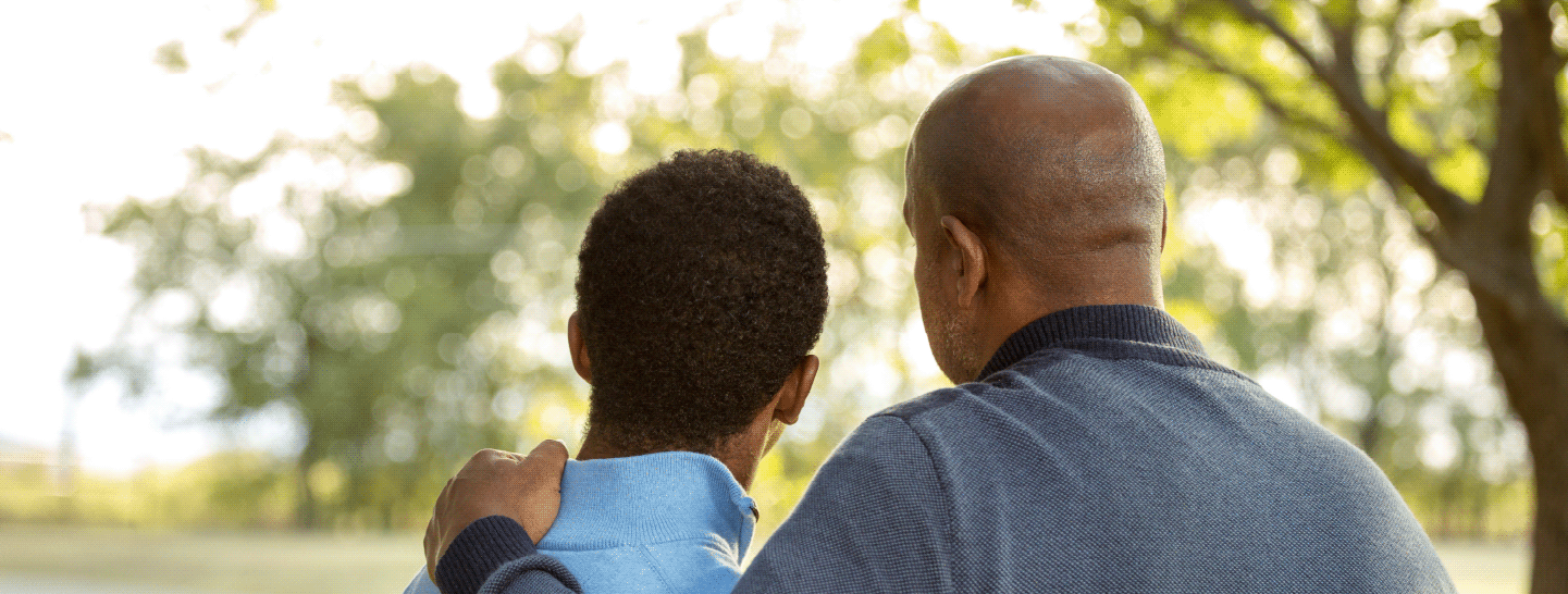 A man comforting his son with a hand on his shoulder outside in a park