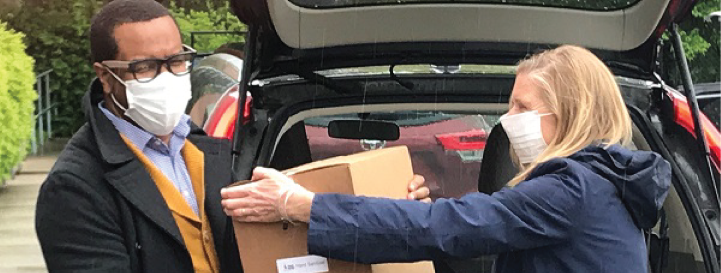 CEO Moira Weir carrying a box of Covid-19 relief supplies