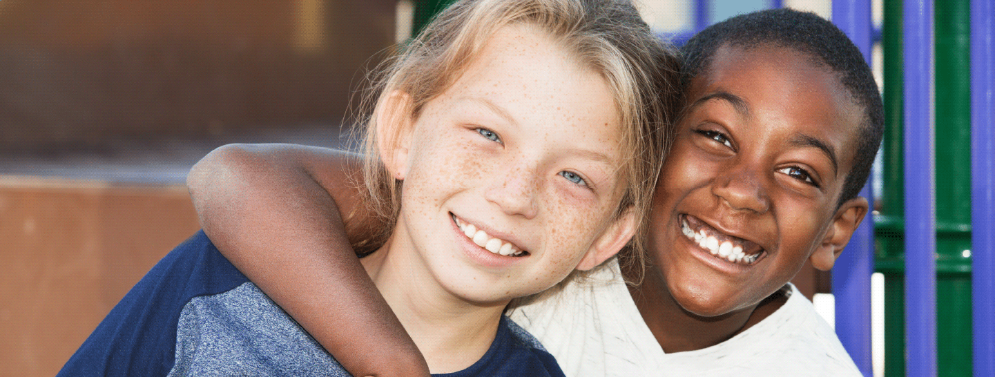 Two children hugging and smiling on a playground