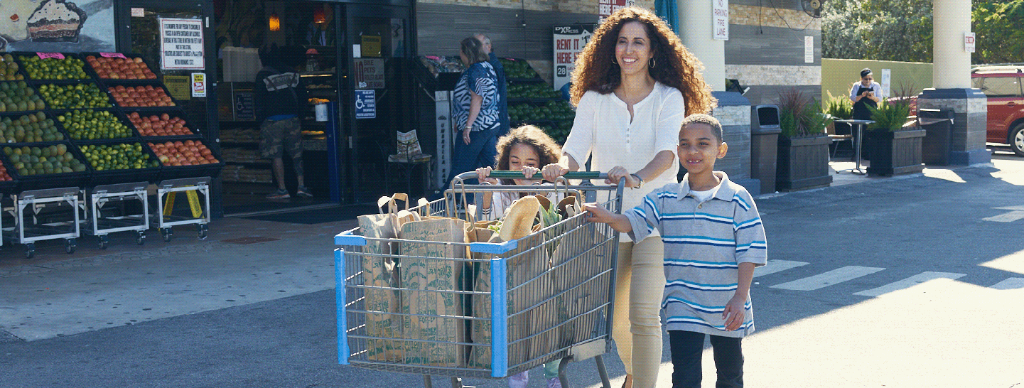 Mother pushing a shopping chart with her two children outside a grocery store
