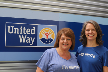 Laura Wells (right) and Taleen Cassidy (left) standing together outside in front of the UWGC sign