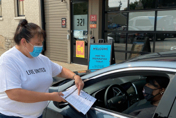 Image of a Free Tax Prep volunteer wearing a mask assisting a customer in their car with their tax forms.