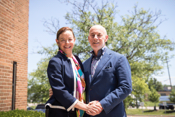 Leaders Society: A man and woman standing together outside in a park