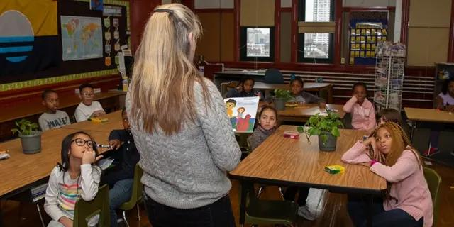 Teacher standing in front of a class while reading a book outloud