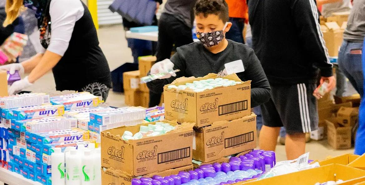 Teenager in front of table full of personal hygiene products, filling a shoebox.
