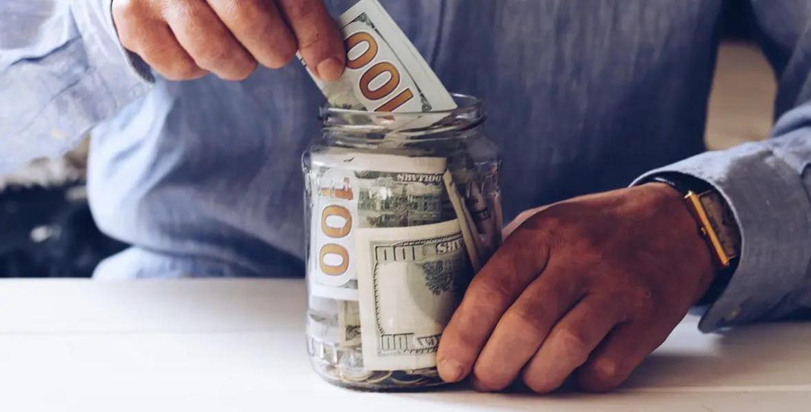 Close up of a man's hands filling a jar with $100 bills.