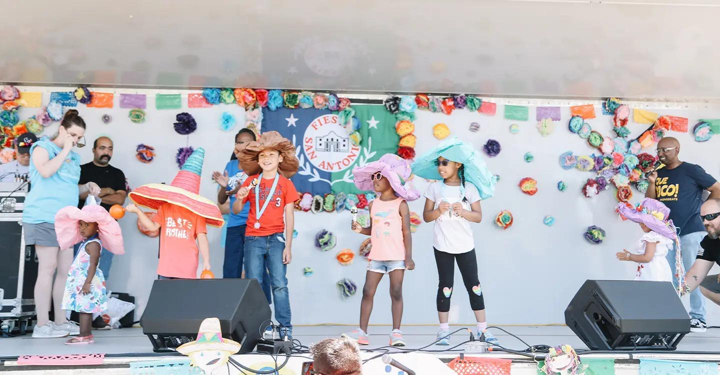 Group of kids in Fiesta hats on a stage.