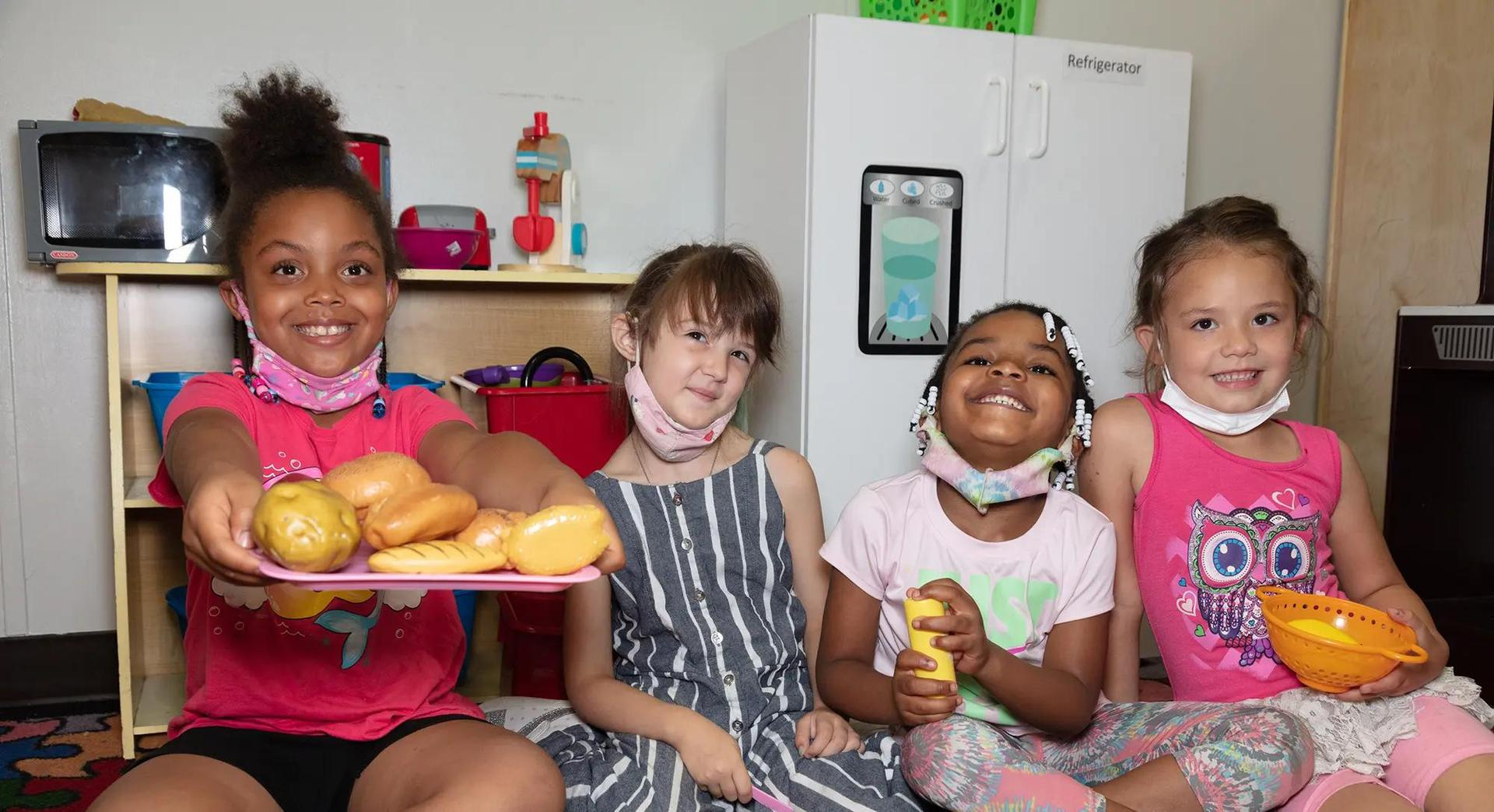 Children holding play food.