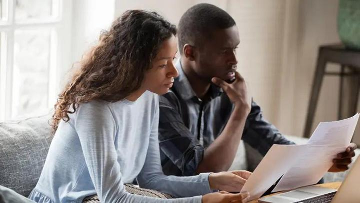 Black couple reviewing paperwork together.