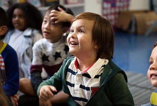 Young child sitting with other children at daycare.