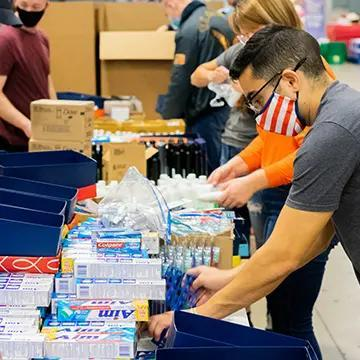 Volunteer filling shoebox with hygiene products.
