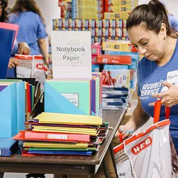 Woman volunteer filling bag with school supplies.