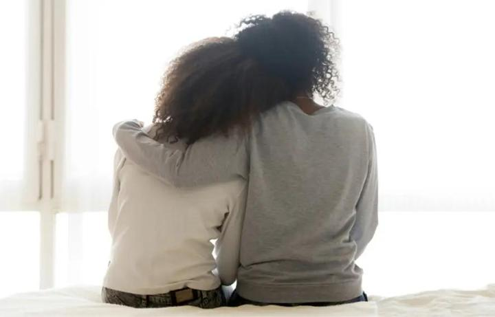 Back view of two women leaning against each other.