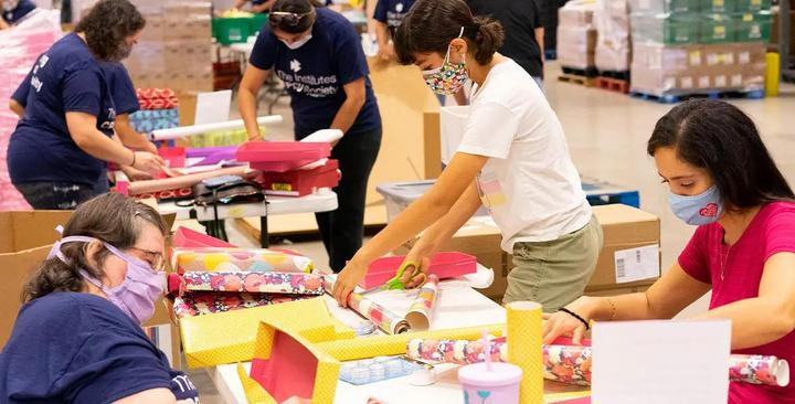 Group of volunteers wrapping and decorating shoeboxes.
