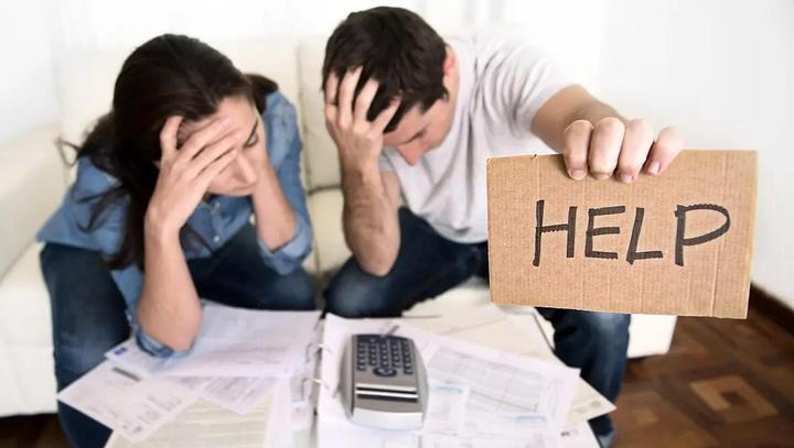 Man holding help sign while working on budget with spouse