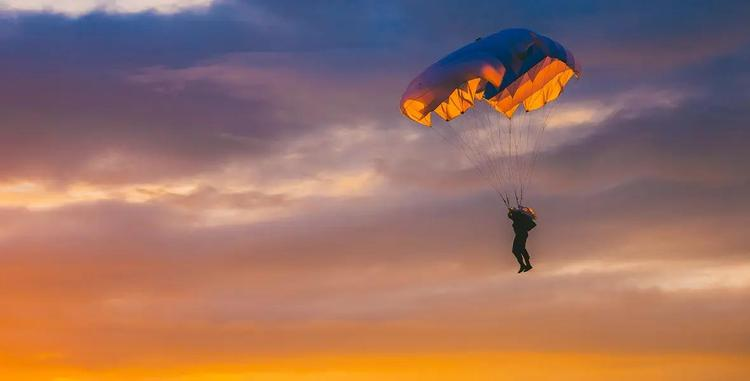 Silhouette of skydiver against a sunset.