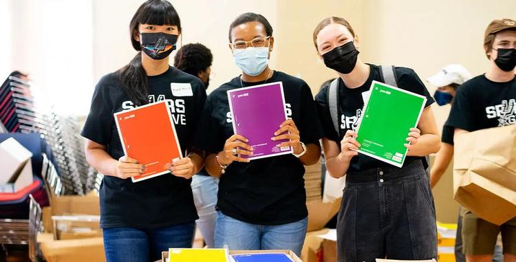 Three people standing together wearing face masks and holding notebooks