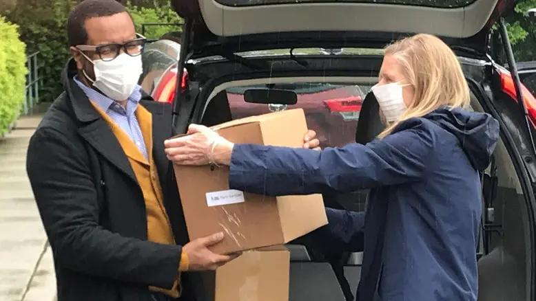 oira Weir, right, CEO of United Way of Greater Cincinnati, passes a box of P&G hand sanitizer to Eddie Koen, CEO of the Urban League of Greater Southwestern Ohio.