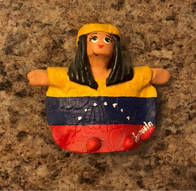 A clay figure of a woman in the Guajiros tribe with the Venezuelan flag on it.