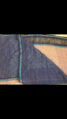 This image shows a navy blue patterned blanket. It was hand woven before I was born. It is made with multiple different materials.
