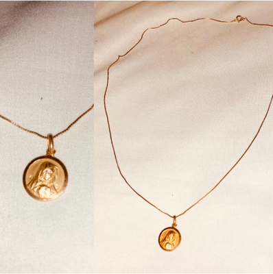 It is a gold necklace with Mary on it.
