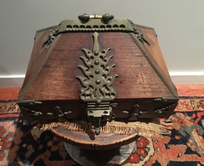 "A dark wooden 10""x10"" box with brass decoration, lock and handle from the 16th century originating from India.  It is historically used as a dowry box."