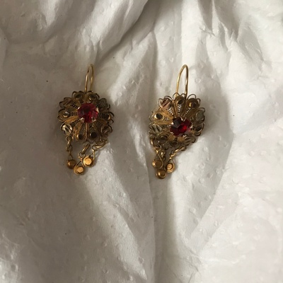 A pair of flower-shaped earrings with three circles hanging at the bottom.