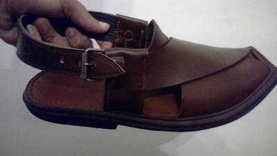Leather shoe with metal buckle strap.