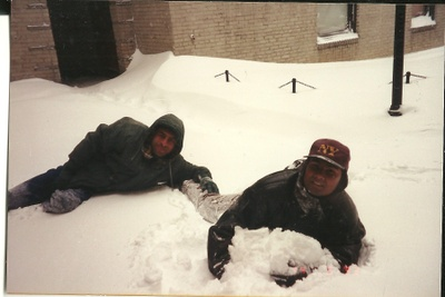 Two men rolling around in the snow.