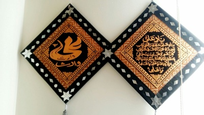 (Islamic Decor in Arabic) The name 'Ali, the helper' written on the left, and the supplication 'Naad-e-Ali' by the Holy Prophet of Islam written on the right.