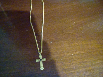 Gold cross necklace with a red ruby.