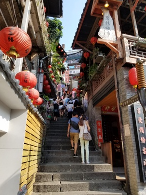 Red lanterns line up along the steps in a Taiwanese village with many modern tourists