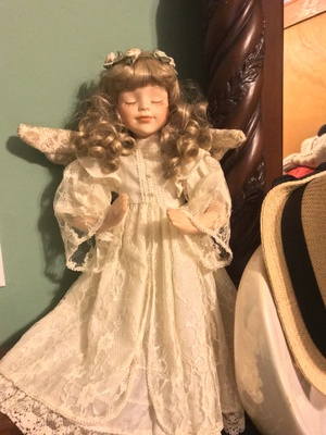 Porcelain doll, blonde curled hair, real hair eyelashes, stuffed wings, and a lace dress with a smile.