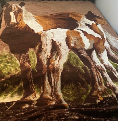 A brown blanket with the image of horses