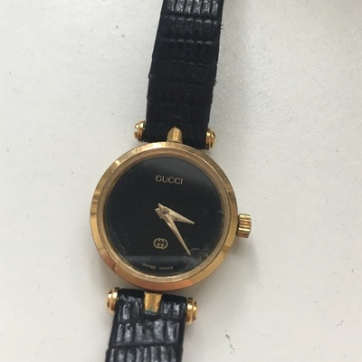 Gold bezel Gucci watch with black strap.