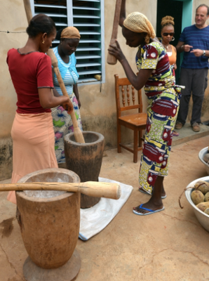 This picture shows some girls that are using the pestle and mortar to bring their ingredients.