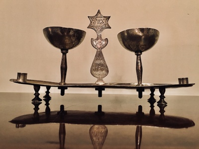 Silver lamp handmade in Afghanistan used to illuminate a room with hand made wicks and oil. It is engraved with hebrew letters that represent the Jewish tradition of lighting a lamp every Sabbath.