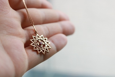 Golden star necklace with a little ruby
