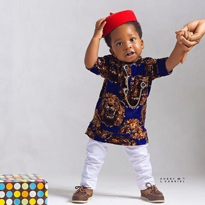 """A Nigerian toddler modeling an Isiagu shirt. """"The Isiagu, also called Chieftaincy, is a pullover shirt similar to the dashiki that is worn by Igbo people. It is usually worn on special occasions like weddings. The shirt may be long or short sleeved. Some shirts have gold buttons that are linked by a chain. There is usually a breast pocket on the front."""""""