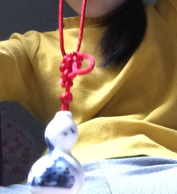 A white pendant hands from a red chord