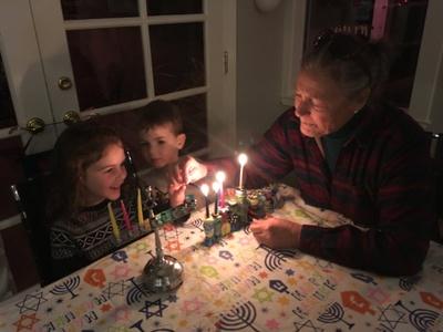 My mom and my kids lighting the menorah.