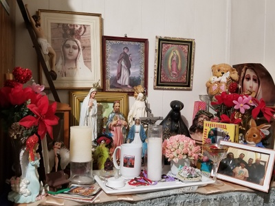 Altar  of candles, statues & photographs
