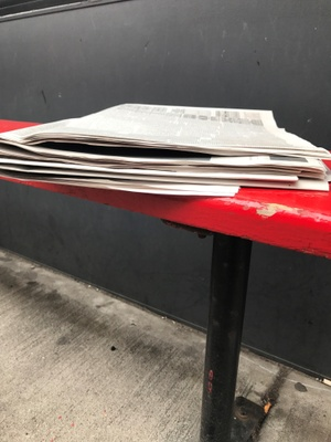 Newspaper sitting on a red bench