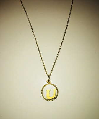 This a golden necklace that displays the first letter of my first name.